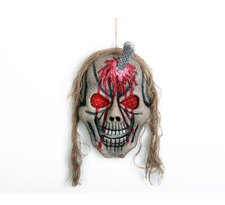 Calavera colgante con melena y con cuchillo clavado de 40x30x8 cm. para Halloween. Artículo muy apropiado para decoración de Halloween.